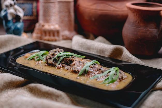 Vista laterale dello stufato di carne con erbe sul tavolo