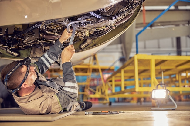 Side view of mechanic repairing the maintenance of a large engine of a passenger airplane in a hangar