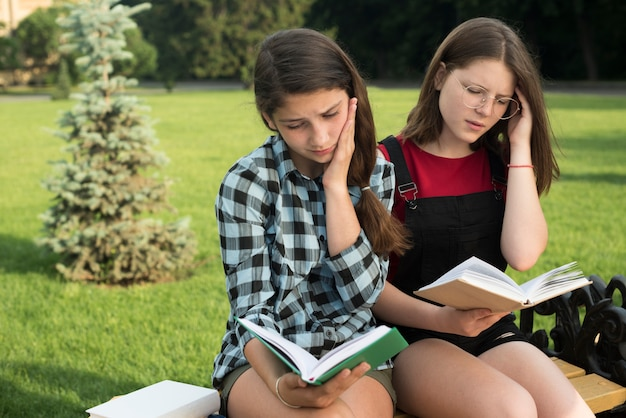 Side view medium shot of highschool girls reading on bench