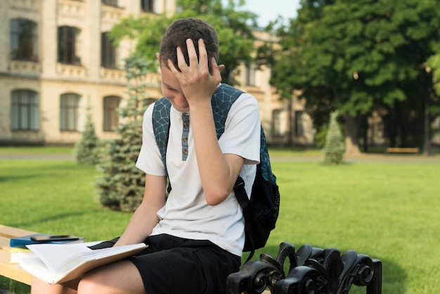 Side view medium shot overwhelmed teenage boy reading