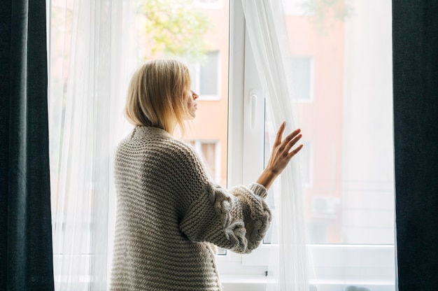 Vista laterale della donna malinconica a casa durante la pandemia guardando attraverso la finestra
