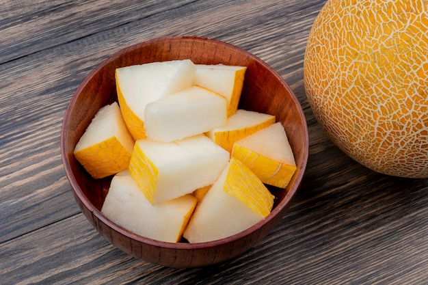 Side view of melon slices in bowl with whole one on wooden background with copy space Free Photo