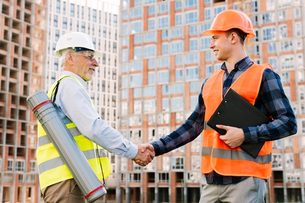 Side view men with safety vests shaking hands