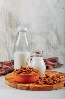 Side view milk carafe and bottle with bowl of almonds on wooden board on white wooden background. horizontal