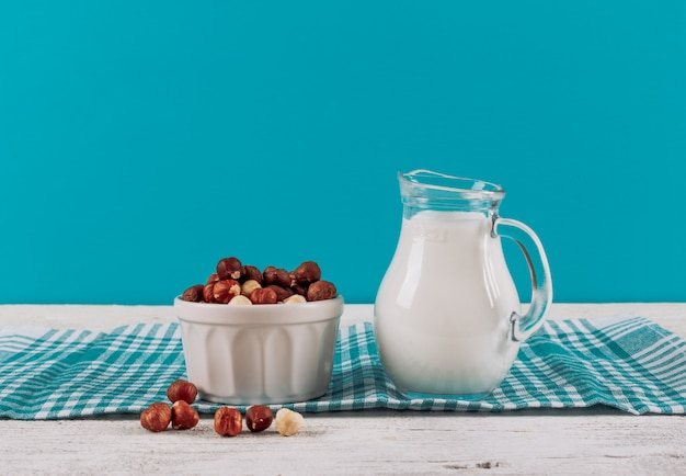Side view milk carafe with bowl of almonds on white wooden and blue cloth background. horizontal space for text