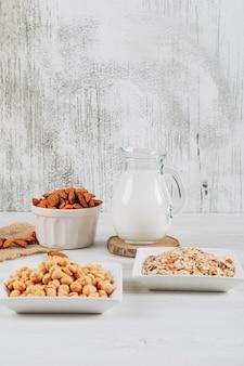 白い木製の背景にアーモンド、ヘーゼルナッツ、オート麦のボウルとサイドビューミルクデカンタ。垂直