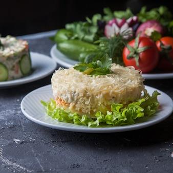 Салат с мимозой, оливковым салатом, помидорами и огурцами в белой круглой тарелке