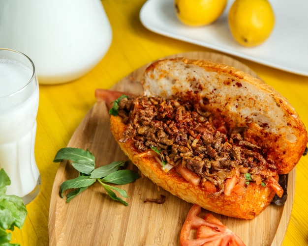 Side view of minced meat with vegetables in bread served with fresh tomatoes and lemon on wooden board