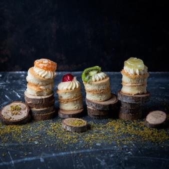 Mini torte vista laterale con panna e frutta in legno