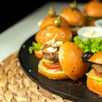 Side view mini meat burgers with olives