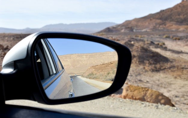 Side view mirror of a car , on road