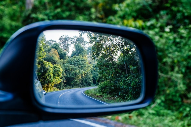 Side view mirror reflection of curve road in the forest.