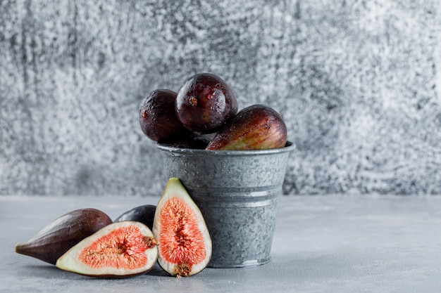 Side view mission figs and halves in bucket on textured background. horizontal space for text