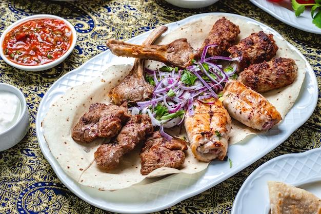 Вид сбоку микс кебабов с ребрышками из абрикоса, люля тикья и куриными шашлыками с зеленью красного лука на лаваше и томатным соусом на столе