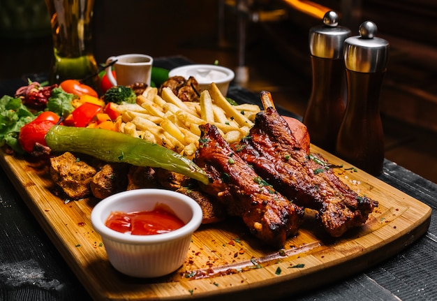 Side view mix of meat snacks with french fries grilled vegetables salad and sauces on the board