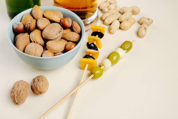 Side view of mix of nuts in a bowl with pickled olives and beer on white with copy space