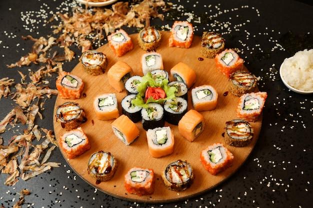 Микс суши-роллов на подносе с имбирем и васаби, вид сбоку