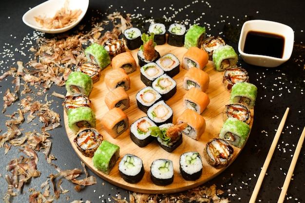 Микс суши-роллов на подносе, вид сбоку с имбирем васаби и соевым соусом
