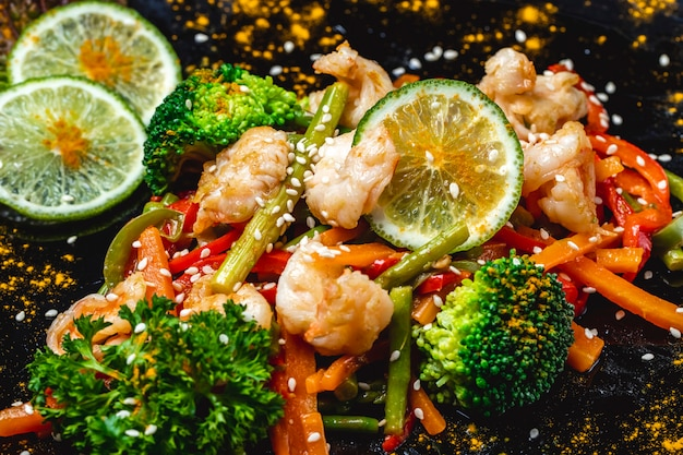 Вид сбоку смешать овощи гриль креветки с брокколи морковь болгарский перец зеленая фасоль ломтики лайма и кунжута на тарелке