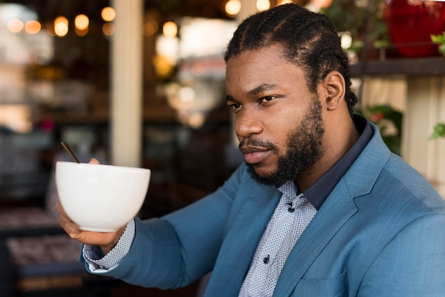 Side view modern man drinking his coffee in a restaurant