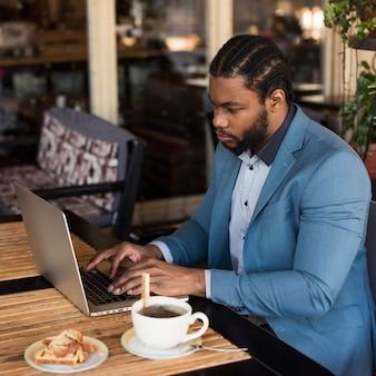 Вид сбоку современный человек, работающий на своем ноутбуке в ресторане