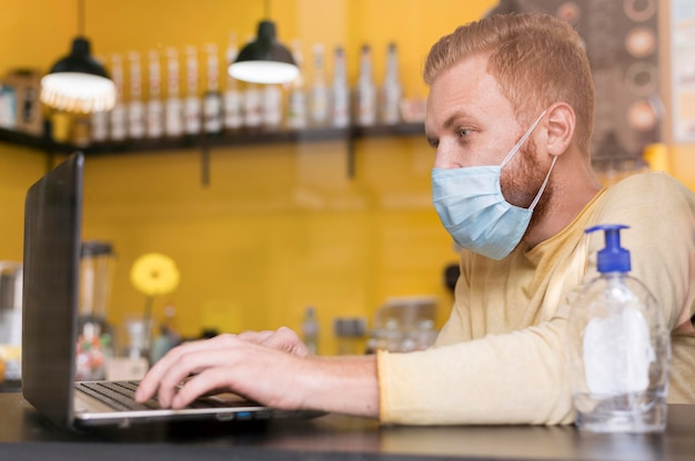 Side view modern man working while using medical mask