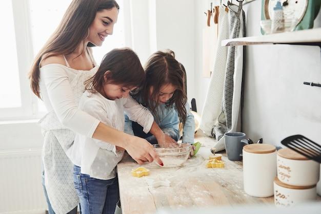 Вид сбоку. мама и две маленькие девочки на кухне учатся готовить хорошую еду с мукой