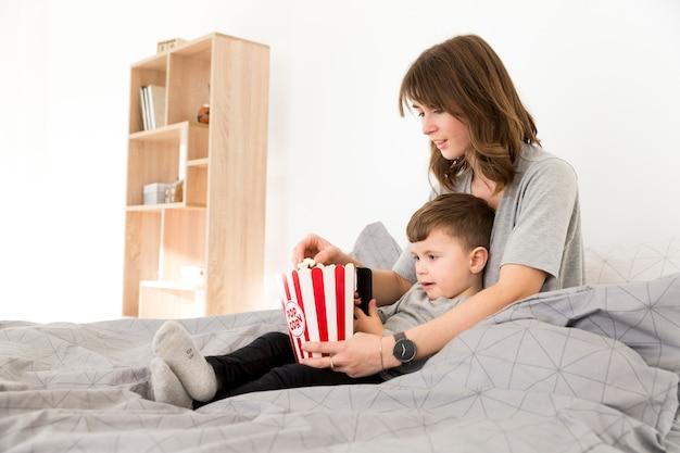 Mamma e figlio di vista laterale che mangiano popcorn