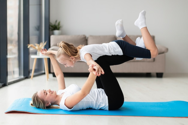 Side view of mother and child working out at home