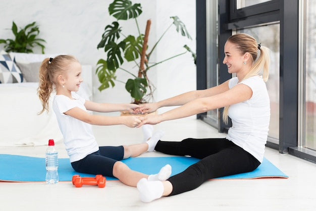 Side view of mother and daughter exercising on yoga mat