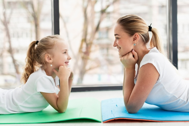 Side view of mother and daughter posing at home on yoga mat