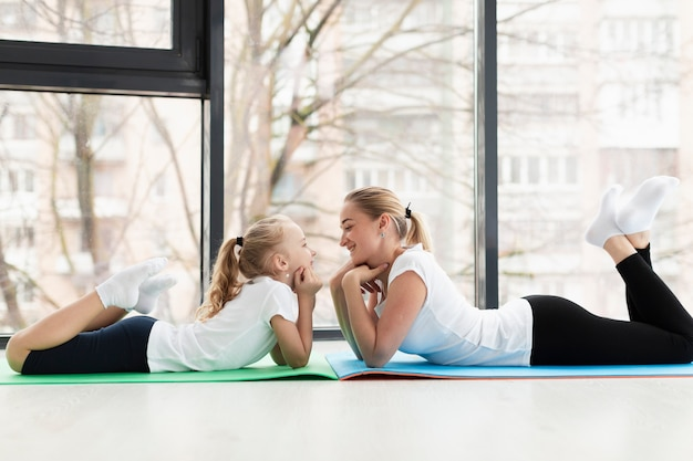 Side view of mother and daughter posing on yoga mat