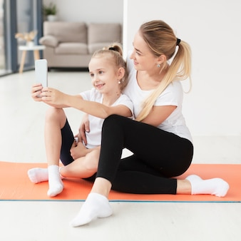 Side view of mother and daughter taking selfie on yoga mat