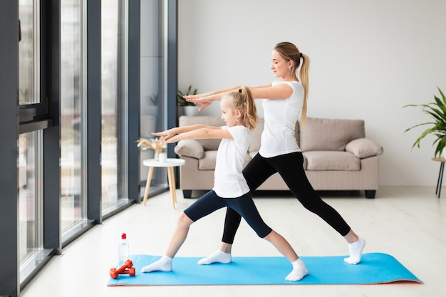 Side view of mother exercising along with child at home