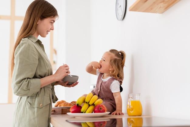 Вид сбоку кормление дочери матерью