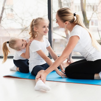 Side view of mother helping daughter practice yoga at home