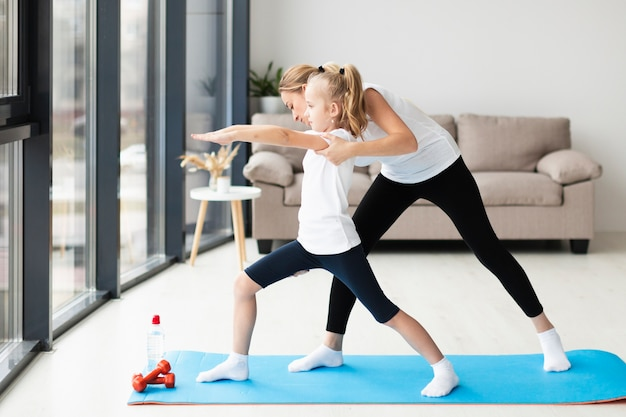 Side view of mother helping daughter do yoga