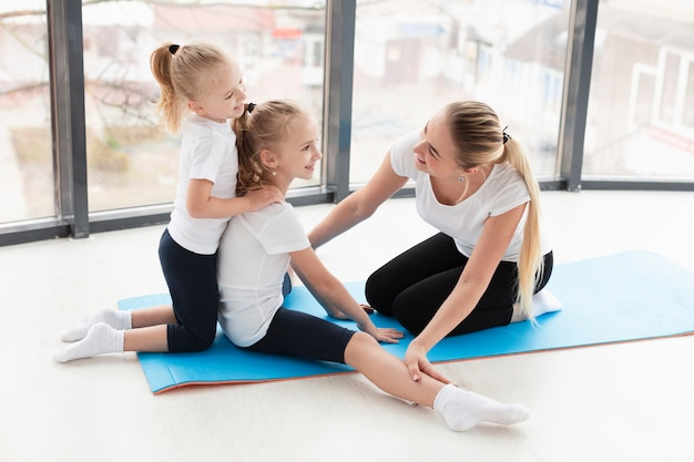 Side view of mother helping daughters exercise at home