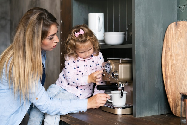 Side view mother making coffee with daughter