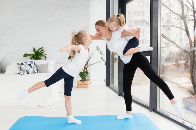 Side view of mother practicing yoga with daughters
