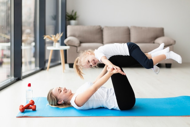 Side view of mother and smiley child working out at home