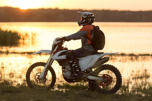 Боковой вид наездника мотоцикла наслаждаясь природой