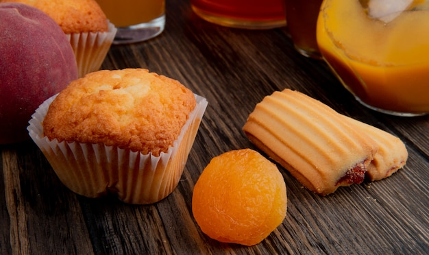 Side view of muffin with dried apricots and cookies on rustic wood