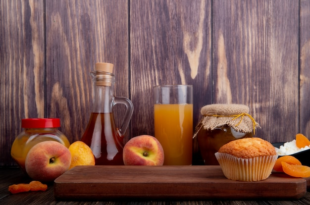 Side view of a muffin on wooden board and fresh ripe peaches with a glass of peach juice and peach jam in a glass jar on rustic background