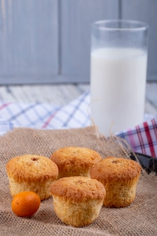 Side view of muffins and a glass of milk on the table