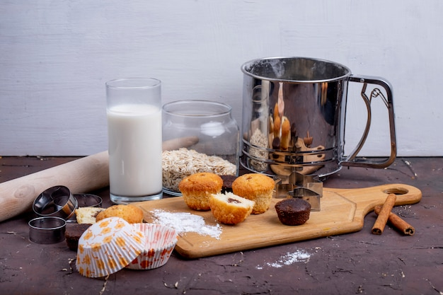Side view of muffins and a glass of milk on a wooden cutting board