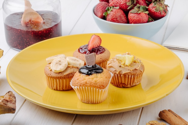 Side view muffins with bananas strawberries chocolate and lemon on a yellow plate