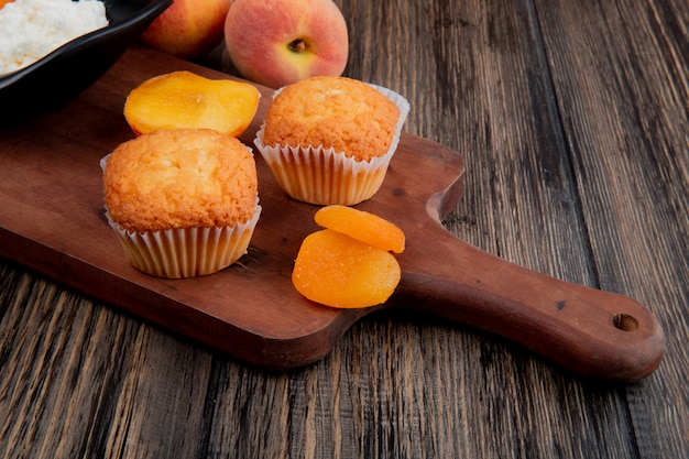 Side view of muffins with dried apricots on wood cutting board and fresh peaches on rustic