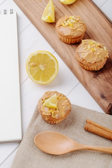 Side view muffins with half a lemon on a blackboard with a spoon and a notebook on a white surface