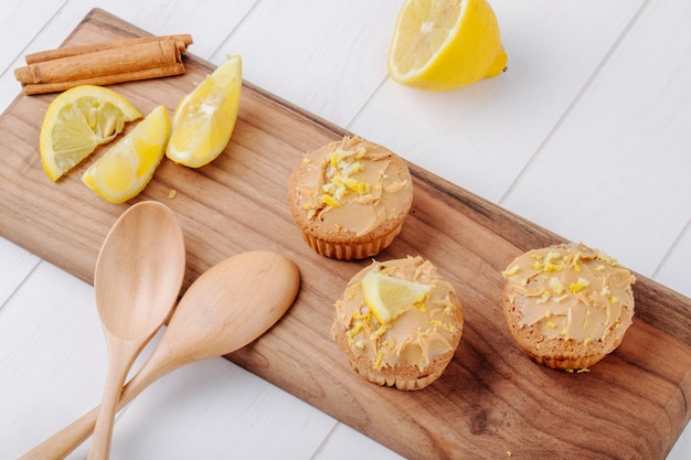 Side view muffins with lemon and cinnamon on a board with wooden spoons